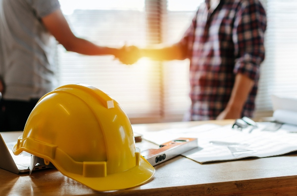 Two parties agree to a construction plan by shaking hands while a hardhat and project plans sit in the foreground.